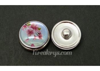 Bouton pression fleur de cerisier rose sur fond bleu clair