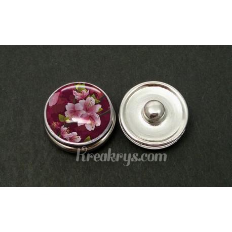 Bouton pression fleur de cerisier rose sur fond bordeau