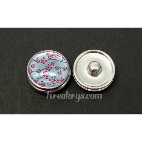 Bouton pression petites fleurs de cerisier rose sur fond bleu clair